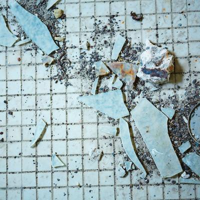 古びたタイルとガラス片の写真