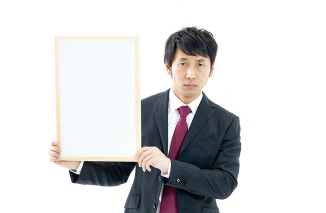 白いフリップを持つ男性会社員の写真