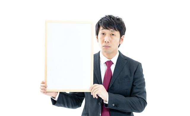 ドヤ顔でフリップを見せる男性の写真