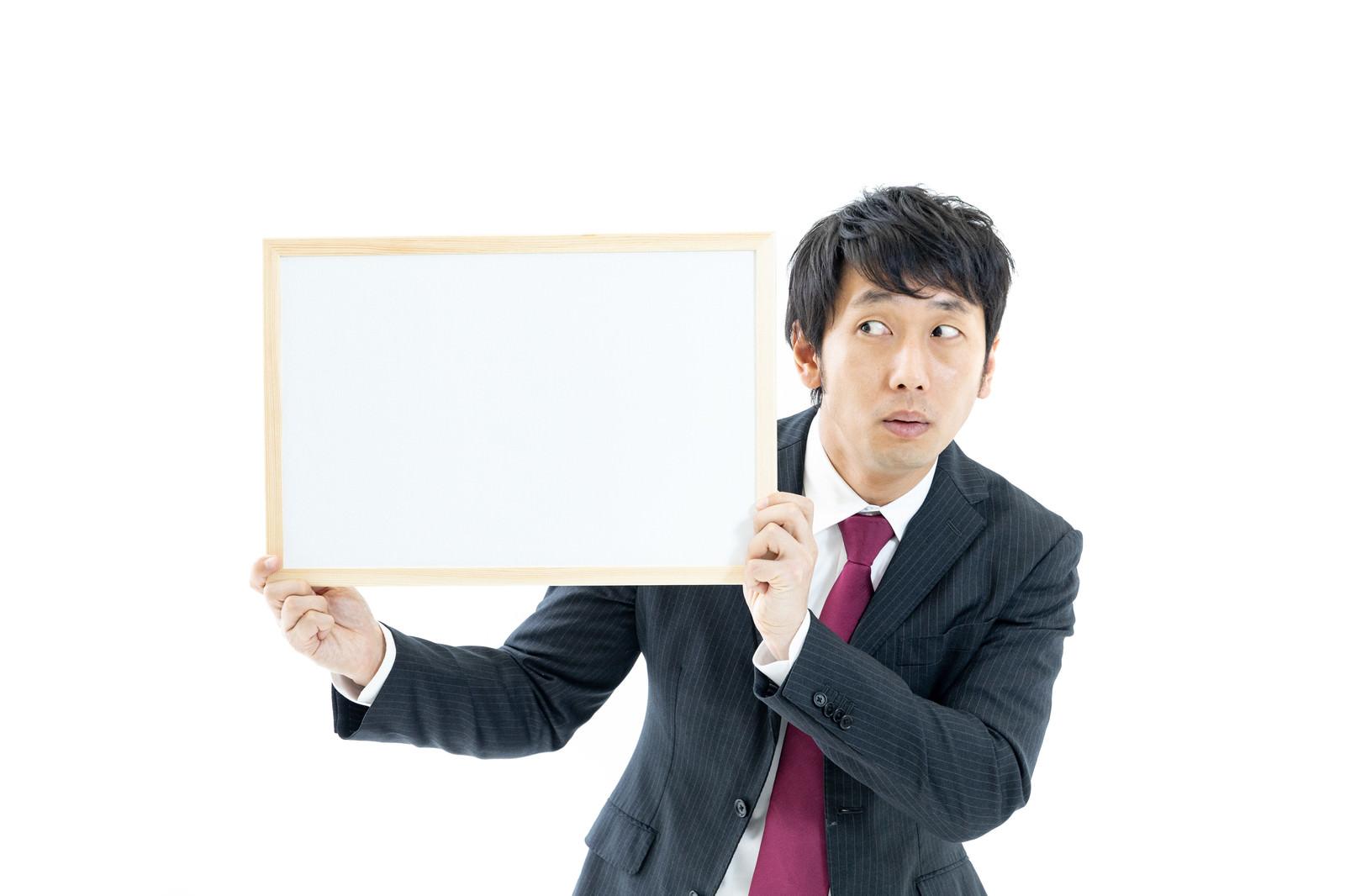 「フリップが見えているか不安になるスーツ姿のディレクター」の写真[モデル:大川竜弥]