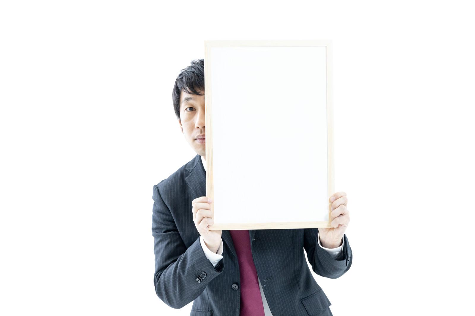 「ホワイトボードからひょっこりする男性」の写真[モデル:大川竜弥]