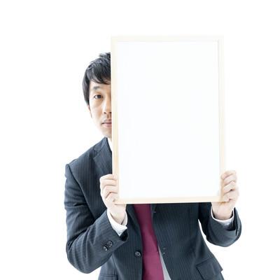 ホワイトボードからひょっこりする男性の写真