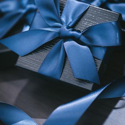 青いリボンが巻かれたプレゼントの写真