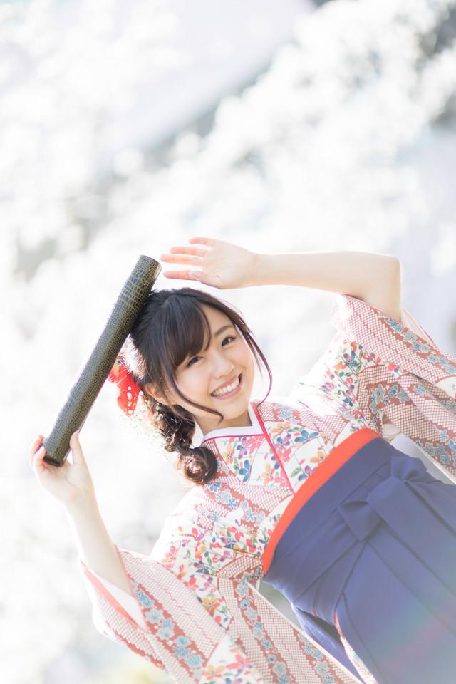 卒業証書の丸筒を持って喜ぶ袴姿の女子大生の写真
