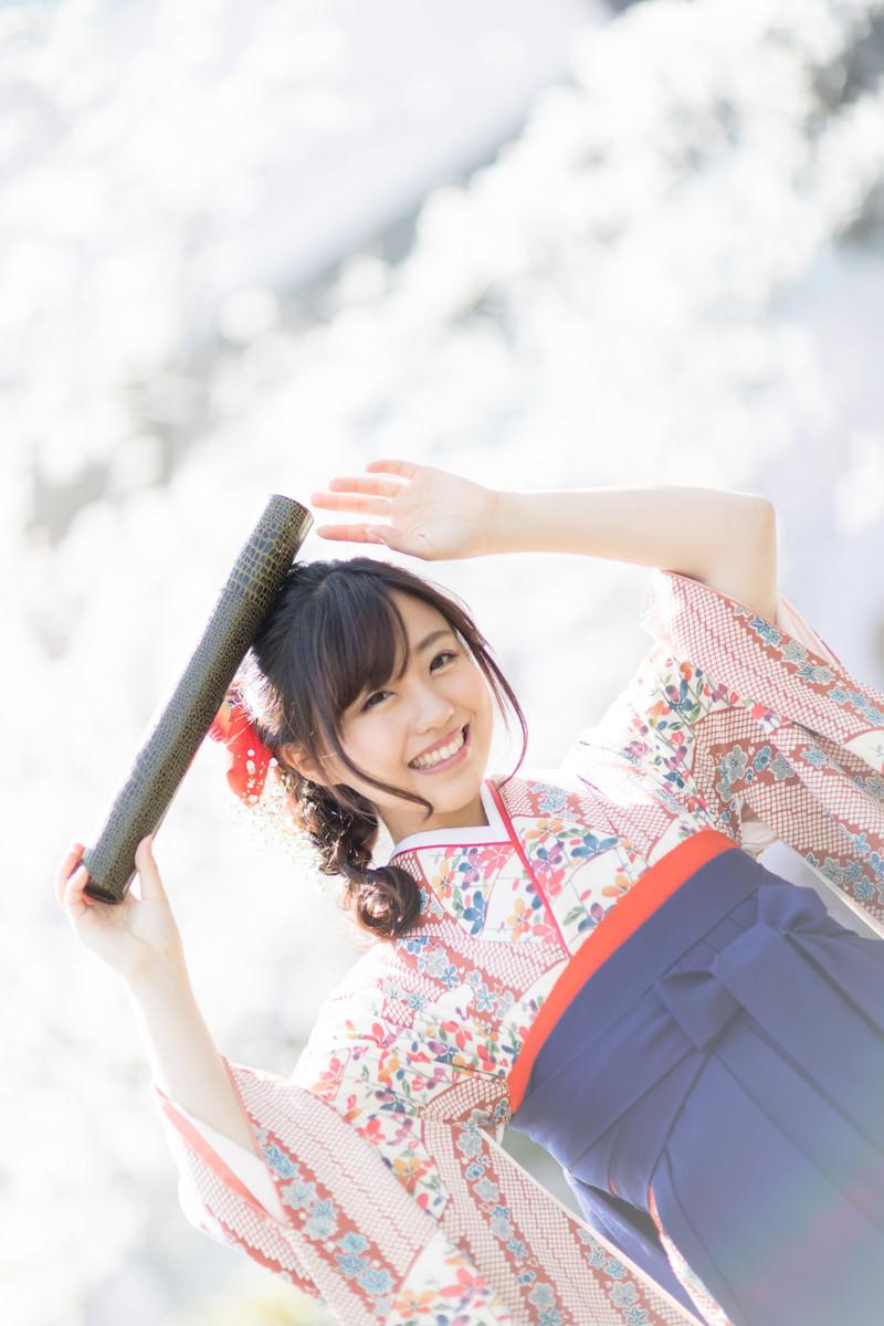 「卒業証書の丸筒を持って喜ぶ袴姿の女子大生」の写真