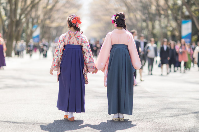 卒業式に2人で手をつなぐ袴女子の後ろ姿の写真