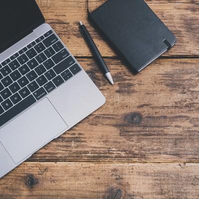 「ノートパソコンと手帳」の写真素材