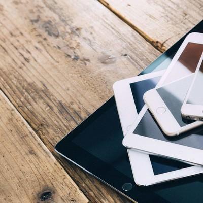 「重ねて置かれたタブレット端末とスマートフォン」の写真素材