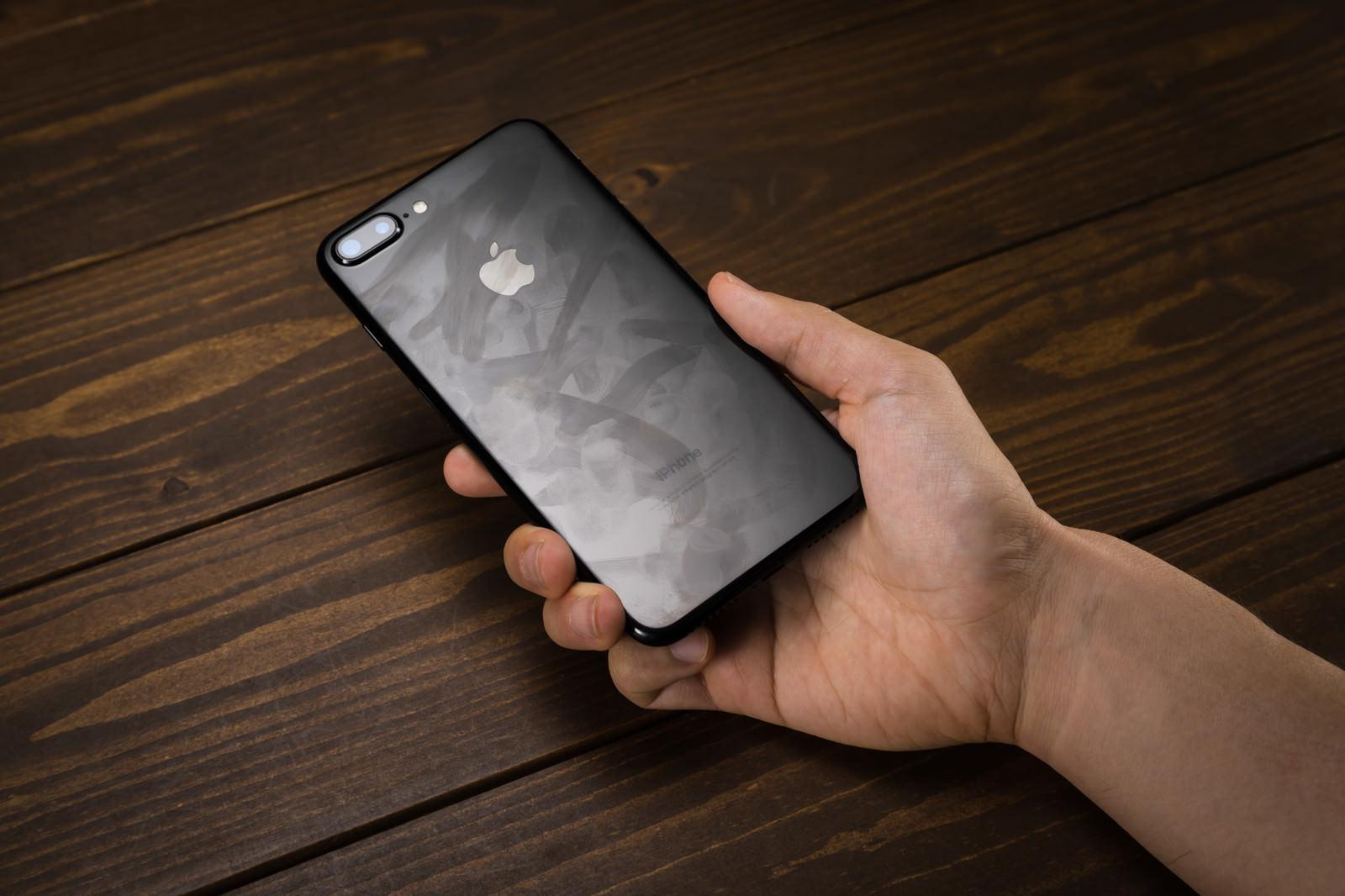 「指紋の跡がべったり残る光沢ボディのスマートフォン」の写真