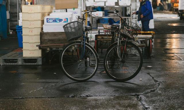 割れたアスファルトと年期の入った自転車(築地市場内)の写真