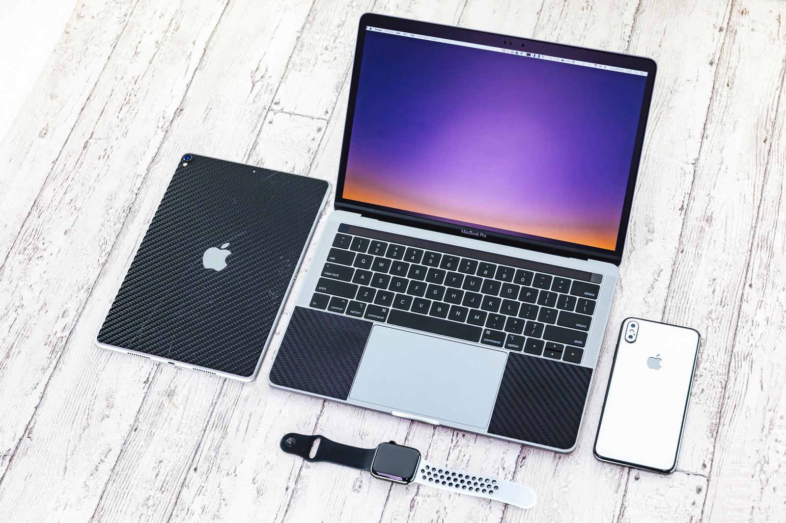 「白を貴重とした床に並べられたApple製品」の写真
