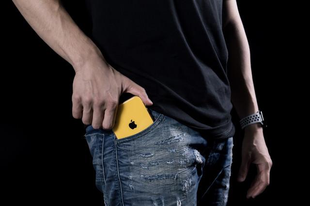 さり気無くポケットに入れる黄色のiPhoneXRの写真