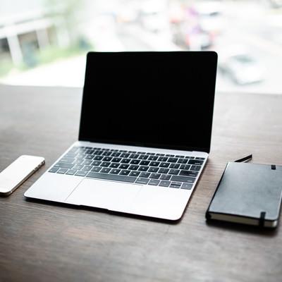 窓際のテーブルに並べられたノートパソコン(iPhone・手帳・ボールペン)の写真
