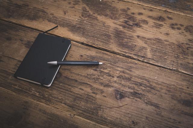 木目のフローリングに置かれた手帳とボールペンの写真