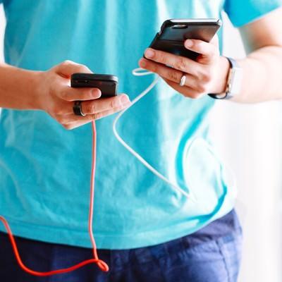 「スマホ両手持ちでゲームするにはモバイルバッテリーが必要」の写真素材