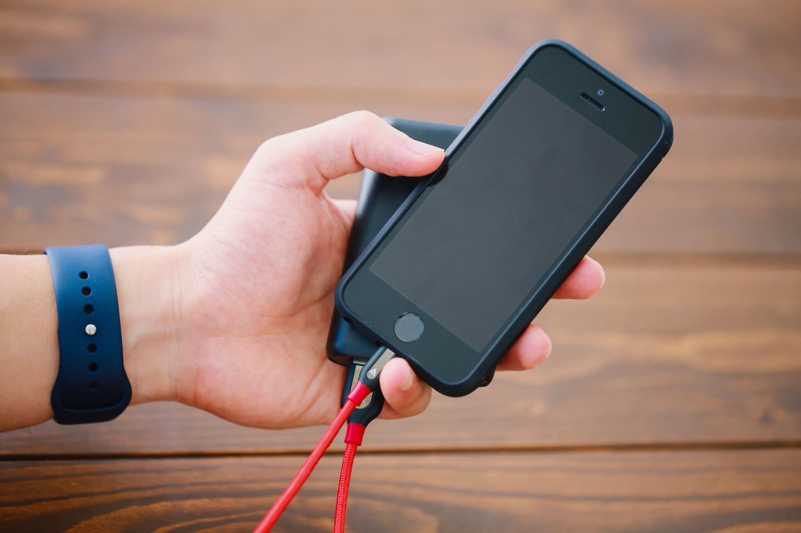 「片手でスマホとモバイルバッテリーを持つスタイル」の写真