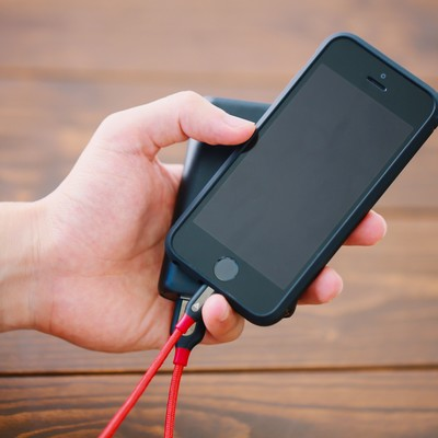 「片手でスマホとモバイルバッテリーを持つスタイル」の写真素材