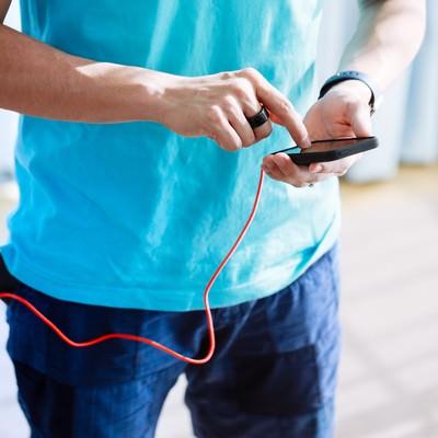 「モバイルバッテリーをポケットに突っ込んで充電しながらスマホでGO」の写真素材
