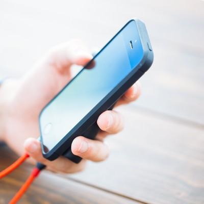 「モバイルバッテリーからチャージしながらスマホを使う」の写真素材