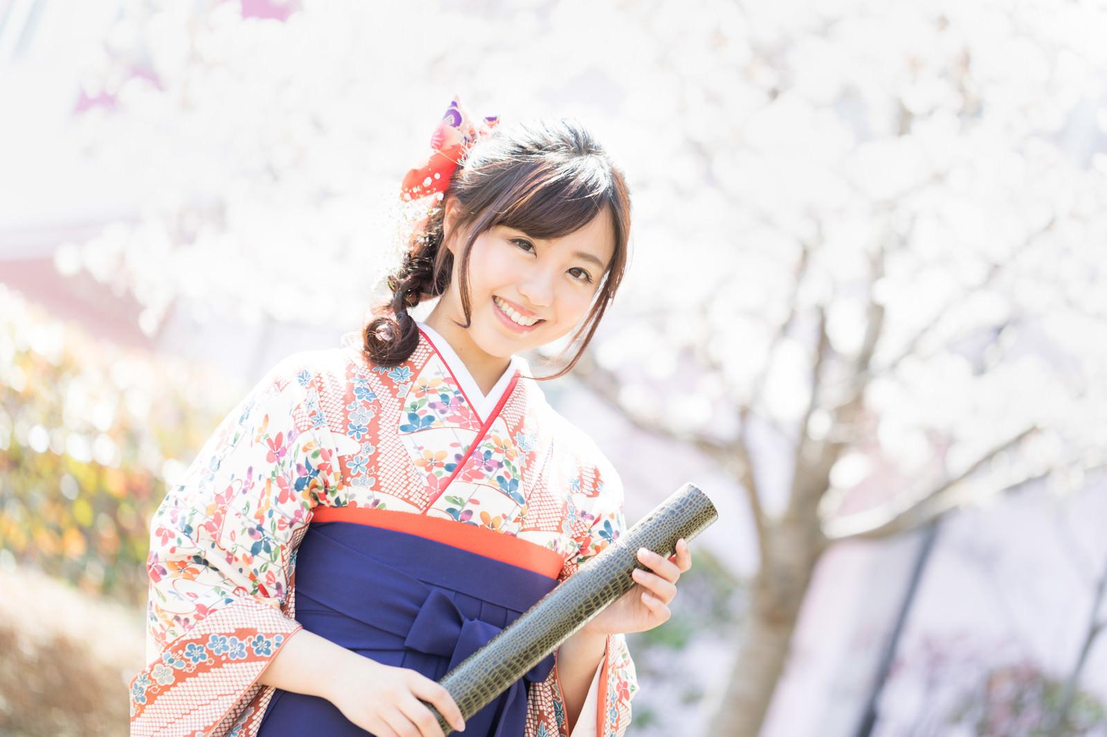 「桜の花と卒業証書を持った袴姿の女性」の写真[モデル:河村友歌]