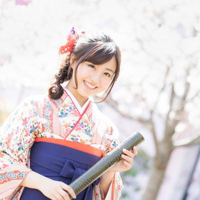 桜の花と卒業証書を持った袴姿の女性の写真