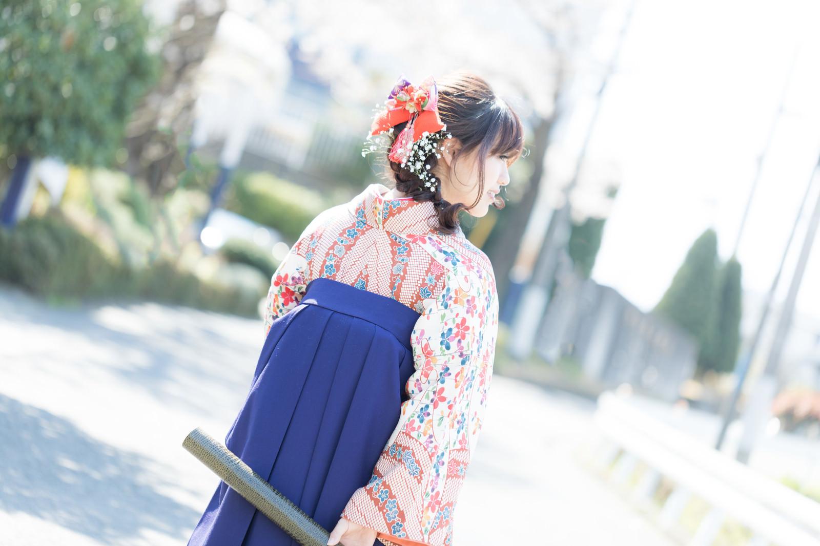 「卒業証書を持った袴姿の女性の後ろ姿」の写真[モデル:河村友歌]