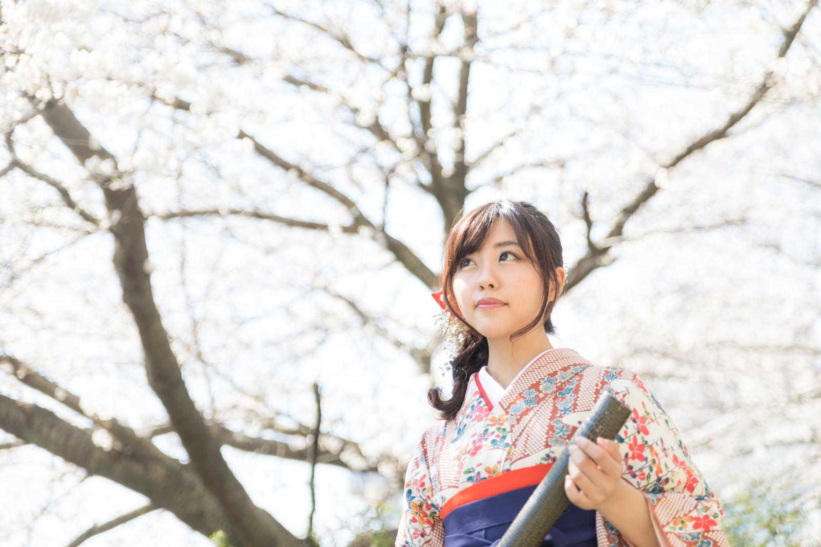 「大きな桜の木の下で卒業の記念撮影」の写真[モデル:河村友歌]