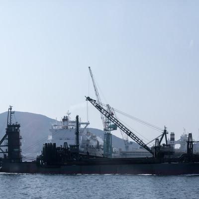 フェリーの後姿と海砂採取船(長崎県)の写真