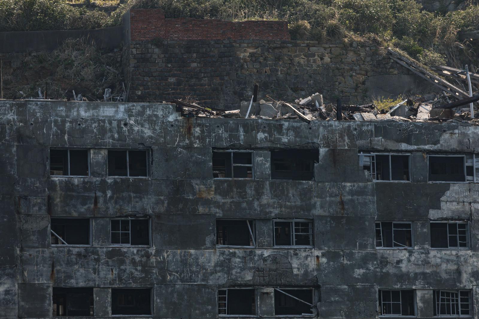 「朽ちた25号棟と瓦礫(軍艦島)」の写真