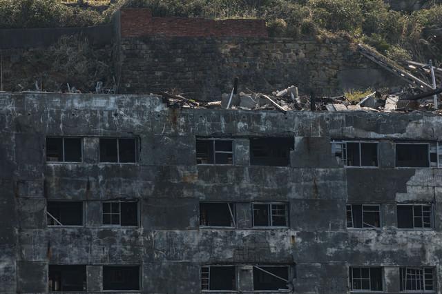 朽ちた25号棟と瓦礫(軍艦島)の写真