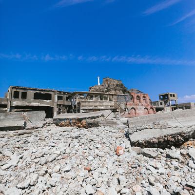 端島炭鉱総合事務所跡越しの肥前端島灯台(軍艦島)の写真