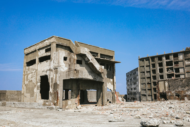 軍艦島の崩れ行く鉄筋の建物と瓦礫の写真