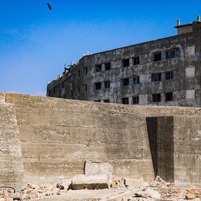 25号棟日給社宅と高い防波堤(軍艦島)の写真