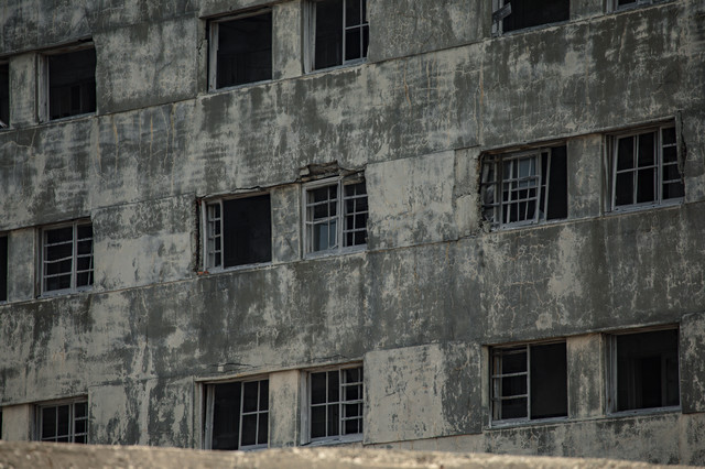 海に面して朽ち果てた日給社宅の窓(軍艦島)の写真