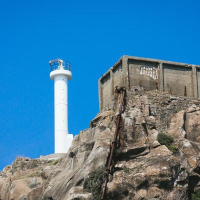 貯水槽と並ぶ肥前端島灯台(軍艦島)の写真