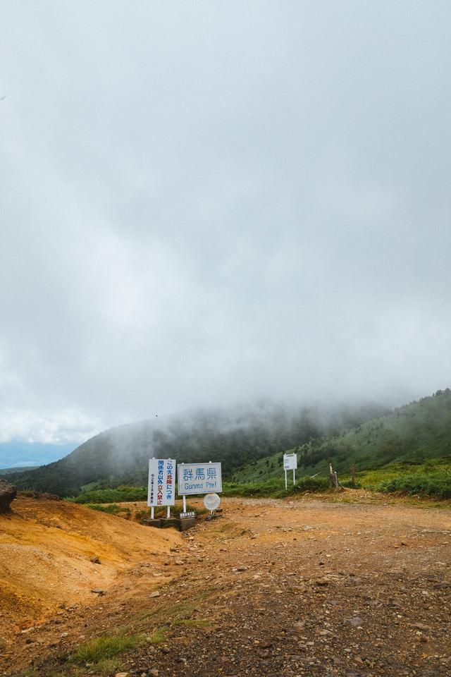 雲に覆われる毛無峠と例の看板の写真