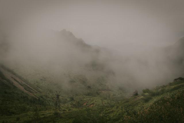 深い霧に包まれた古びた鉄塔の写真