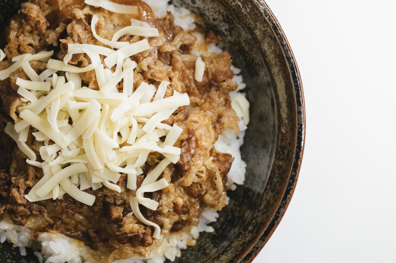 「とろけるチーズがトッピングされた牛丼」の写真