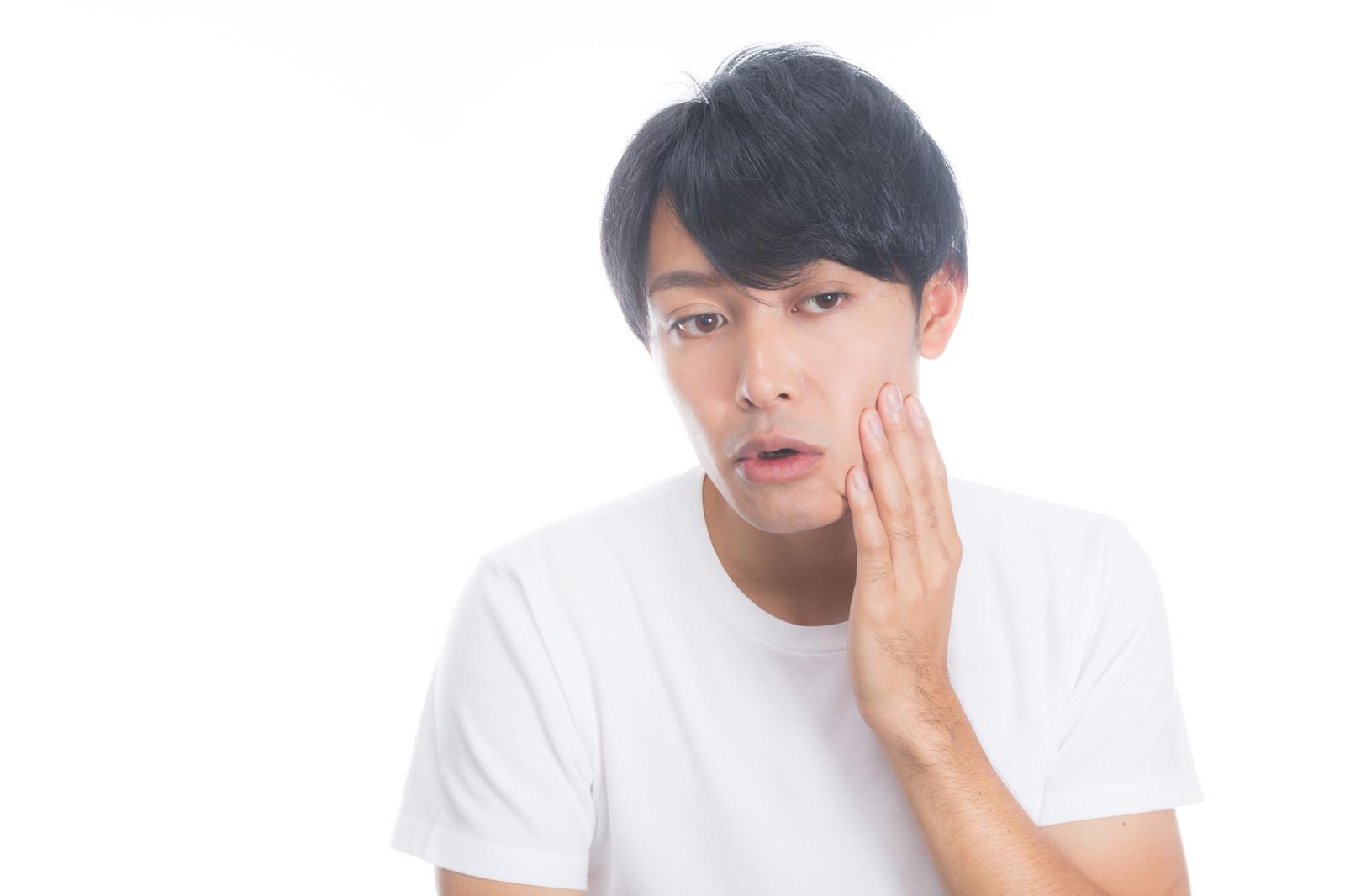 「頬の肌荒れを気にする男性」の写真[モデル:完伍]