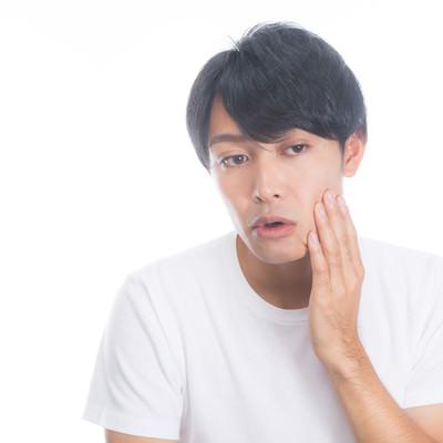 「頬の肌荒れを気にする男性」の写真素材