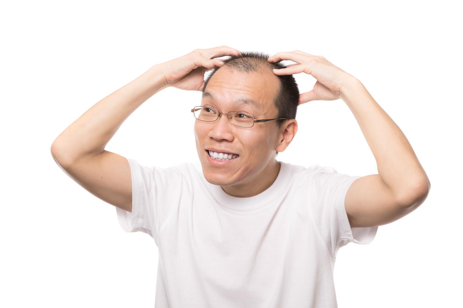 「笑顔で頭皮マッサージする男性」の写真[モデル:サンライズ鈴木]