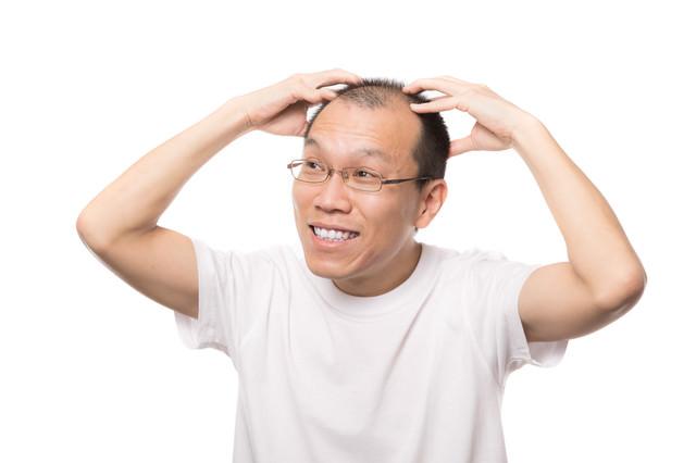笑顔で頭皮マッサージする男性の写真