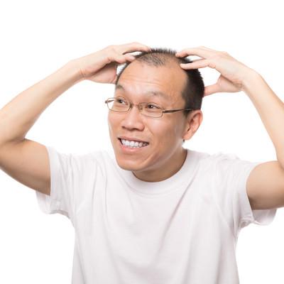 「笑顔で頭皮マッサージする男性」の写真素材