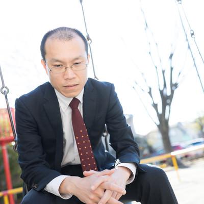 公園のブランコで項垂れる部長の写真