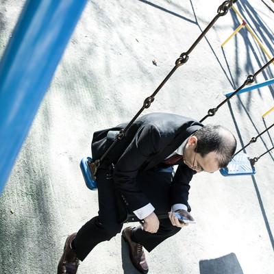 「ストレスを抱えた会社員が公園で項垂れる様子」の写真素材