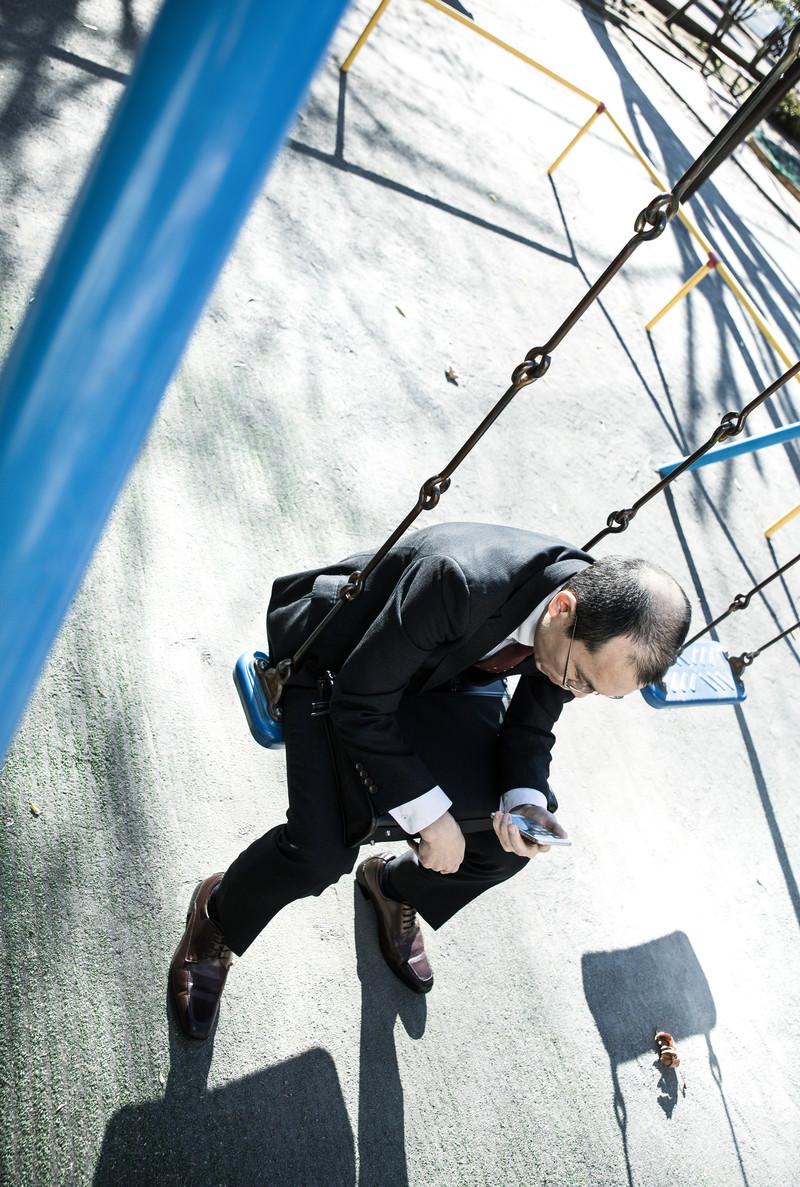 「ストレスを抱えた会社員が公園で項垂れる様子」の写真[モデル:サンライズ鈴木]
