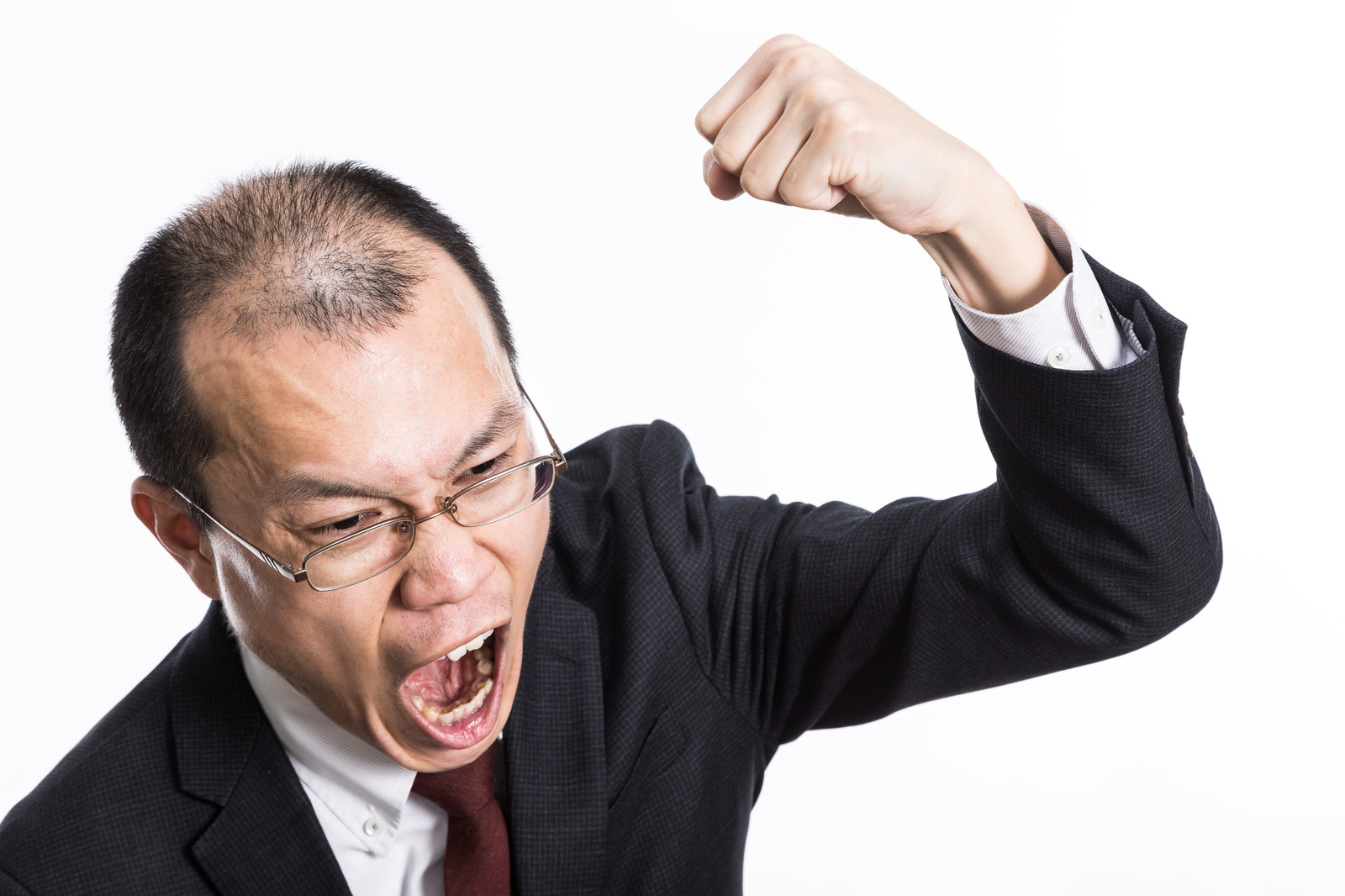 「怒鳴り散らしてこぶしを振り上げるハゲリーマン」の写真[モデル:サンライズ鈴木]