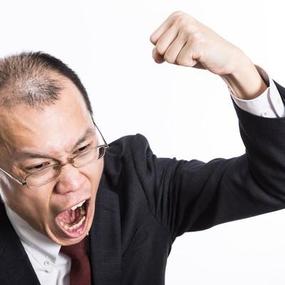 怒鳴り散らしてこぶしを振り上げるハゲリーマンの写真