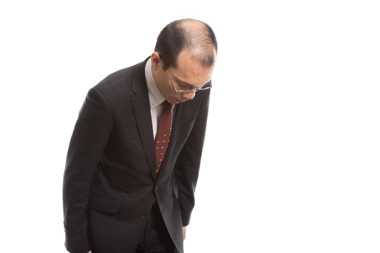 「ハゲを気にしてお辞儀の角度が浅い会社員」の写真[モデル:サンライズ鈴木]