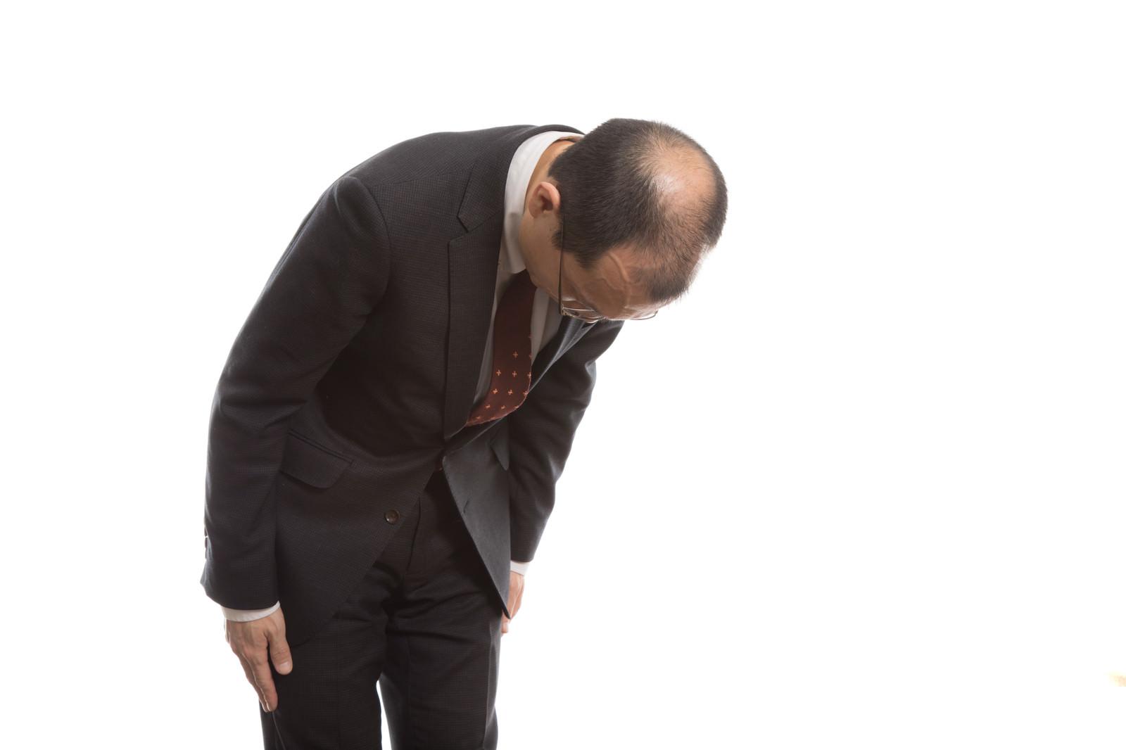 「お辞儀で禿げた頭頂部を見せるサラリーマン」の写真[モデル:サンライズ鈴木]